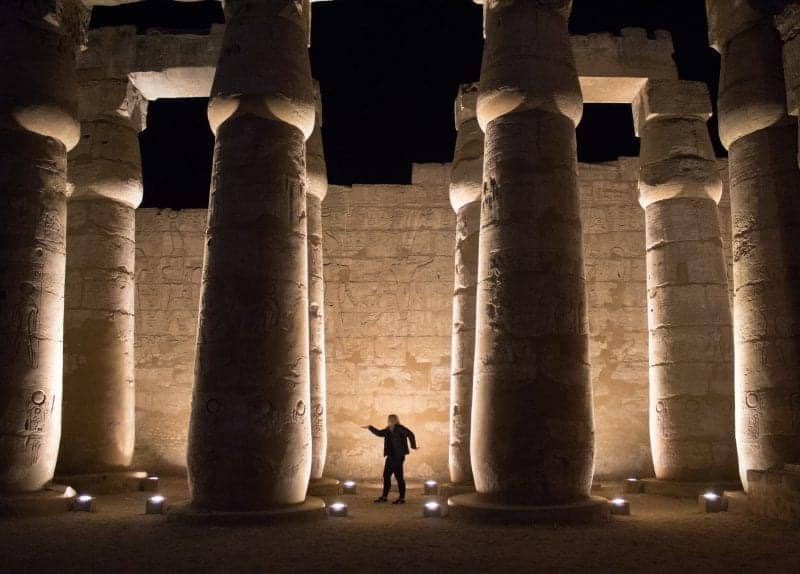 Luxor Temple at night, light up with a girl in the middle doing the 'walk like an Egyptian' pose.