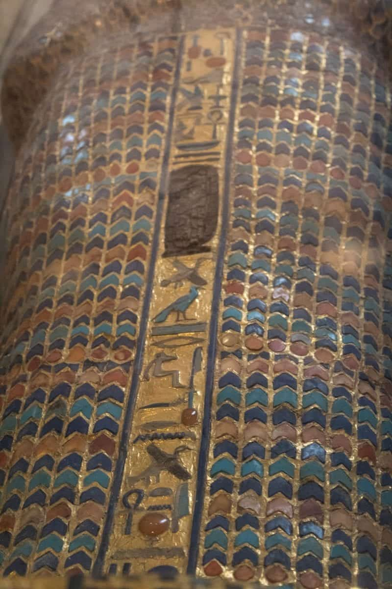A look at a mummy case with beautiful colours in gold, orange dark blue and light blue